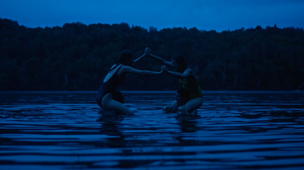 Two couples have chicken fights in a lake at night.